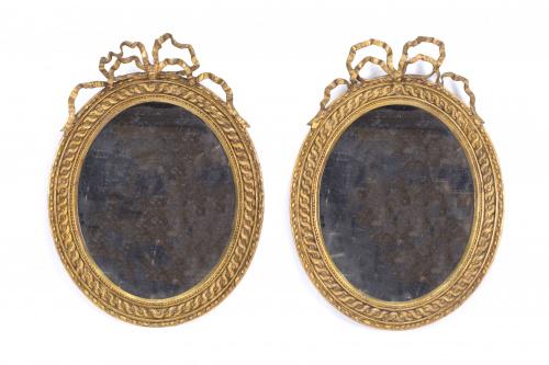 Dos espejos ovalados en madera tallada y dorada.Ffs. S. XI