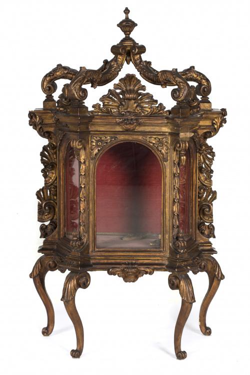"""Vitrina de madera tallada y dorada, con tornapuntas en """"c""""."""