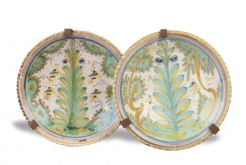 Dos platos acuencados de cerámica con decoración polícroma