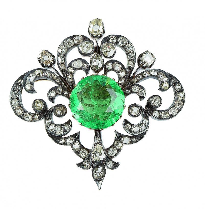 Broche S. XIX con esmeralda central de talla redonda, rodea