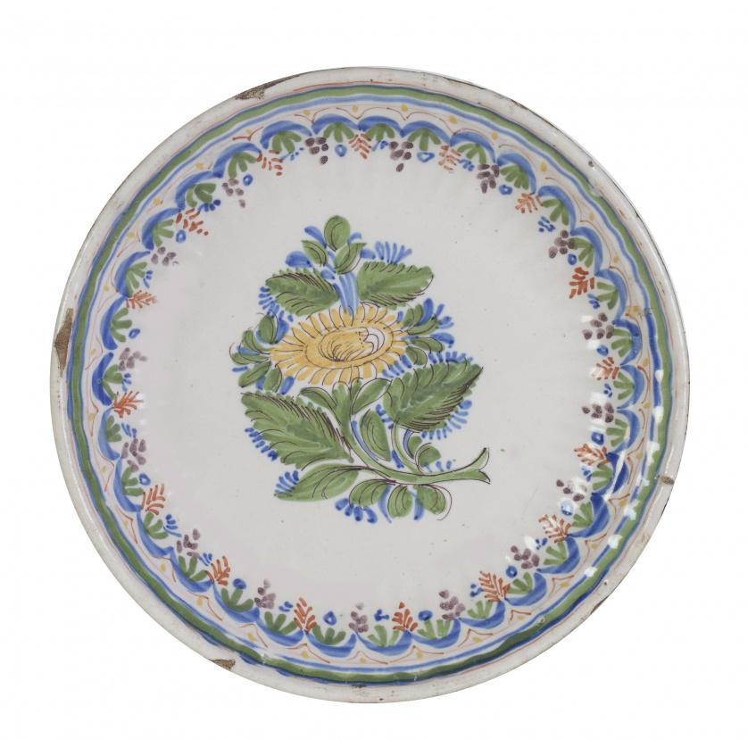 Plato de cerámica levantina, esmaltada con una flor en el a