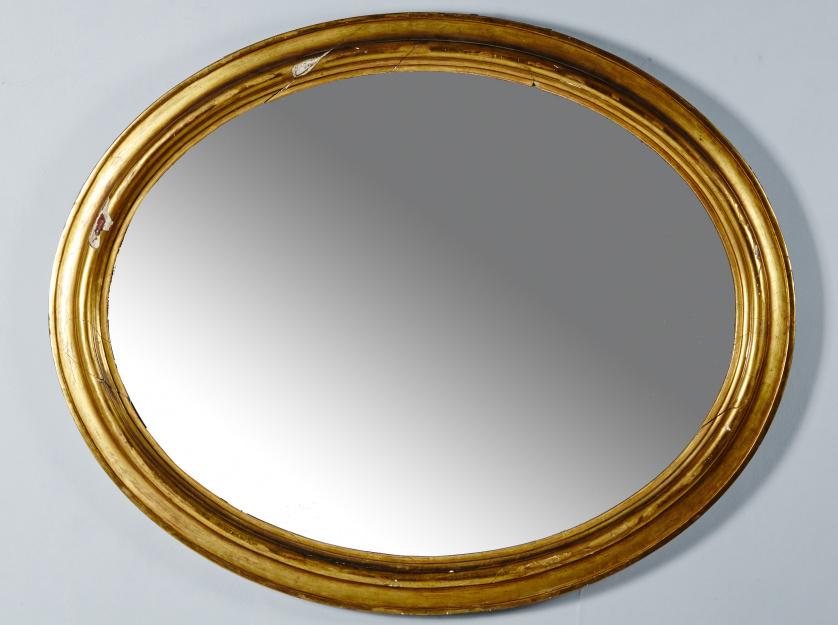 Espejo ovalado en madera tallada y dorada, ff. S. XIX.