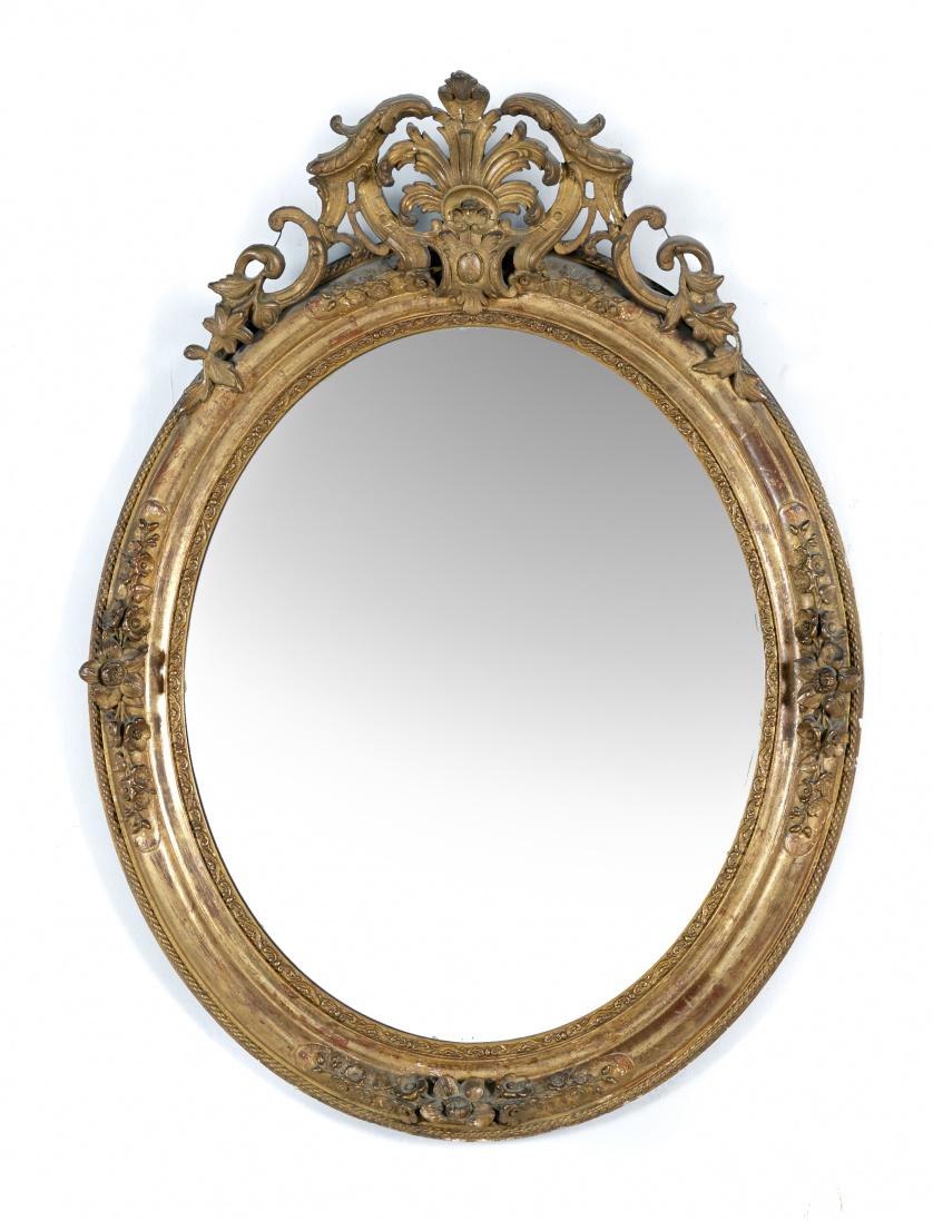 Espejo ovalado con copete de volutas en madera, estucada y