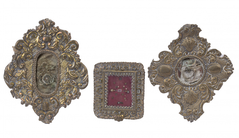 Tres relicarios con marcos de metal repujados y dorados.T