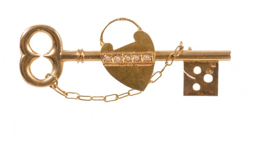 Broche S. XIX en forma de llave con candado central de cora