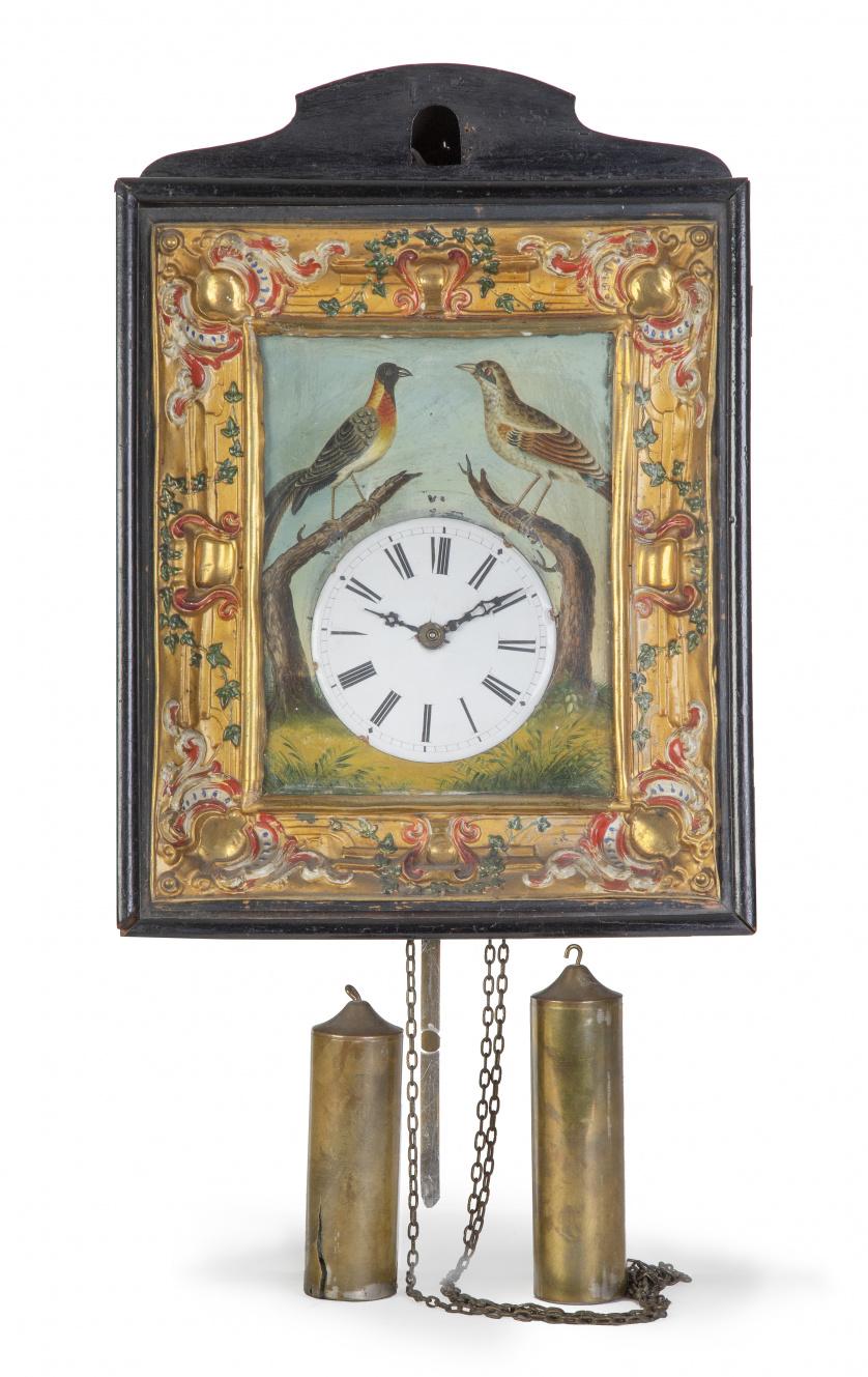 Reloj de pared de metal pintado con marco de madera tallada